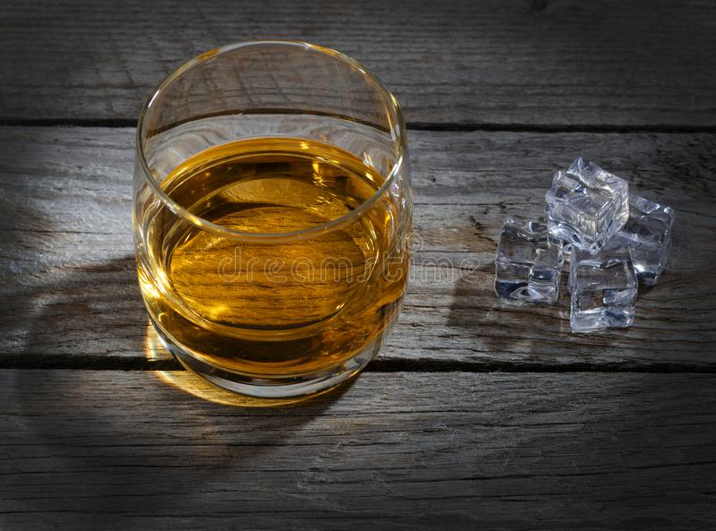 Glas Whisky mit Eiswürfeln auf altem Holztisch lizenzfreie stockfotografie
