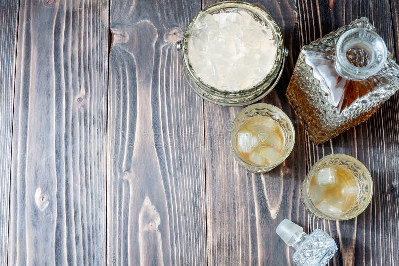 Glas Whisky mit Eiswürfeln und Whiskyflasche auf einem alten Holztisch lizenzfreie stockfotografie