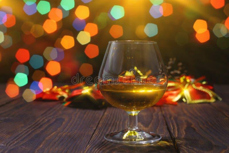 Glas Whisky oder Weinbrand auf Holztisch auf hellem glühendem Hintergrund lizenzfreie stockbilder