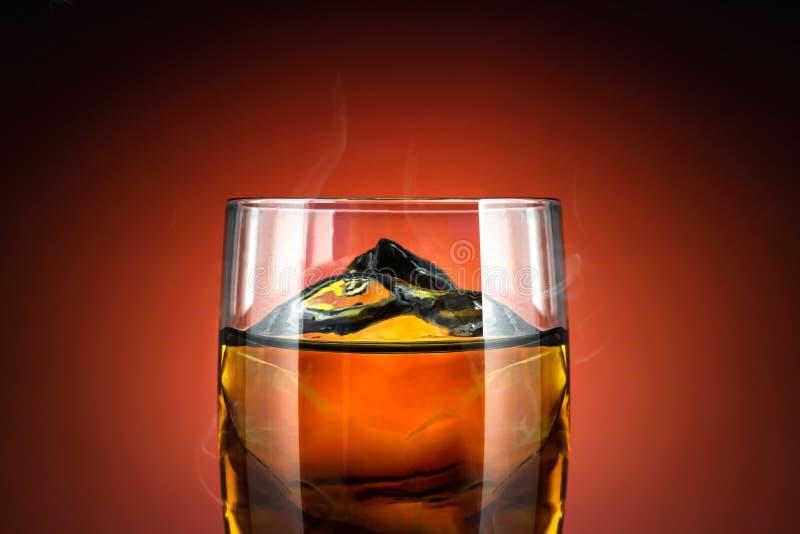 Glas Whisky und Eis auf rotem Hintergrund Schließen Sie oben vom Alkoholglas mit kühlem Getränk lizenzfreie stockfotografie