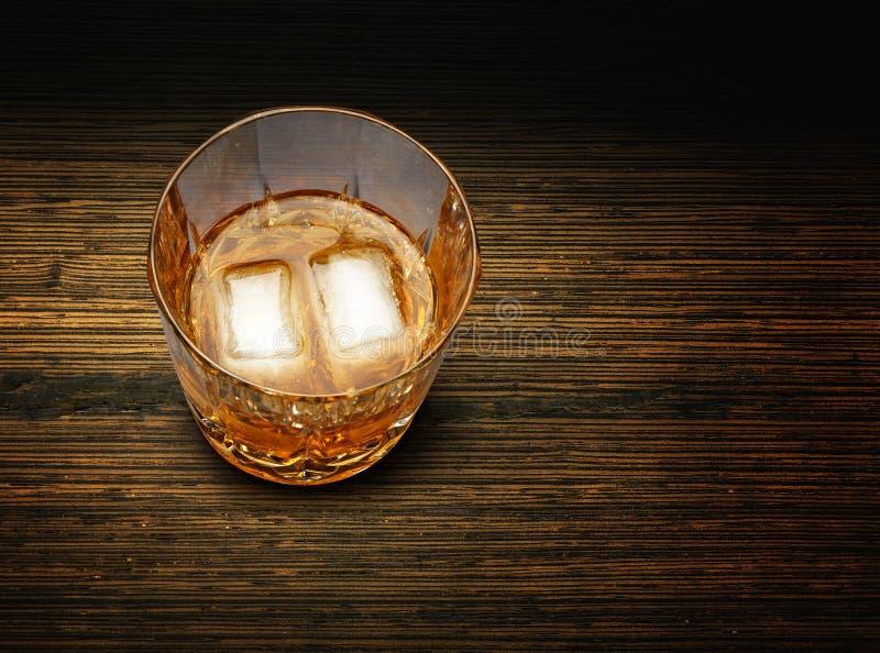 Glas Whisky und Eis auf strukturiertem hölzernem Hintergrund stockfotografie
