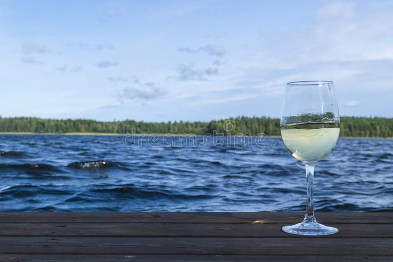 Glas wijn bij een houten pijler De vakantieconcept van de luxetoevlucht Blauw Meer en groene bosachtergrond stock afbeeldingen