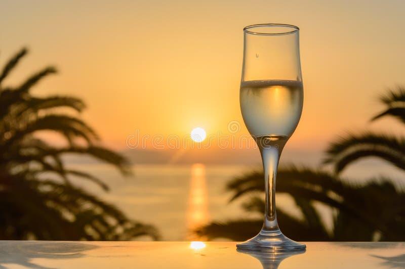 Glas wijn bij zonsopgang op zee stock foto's