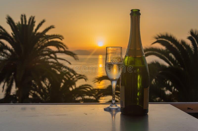 Glas wijn bij zonsopgang op zee stock fotografie