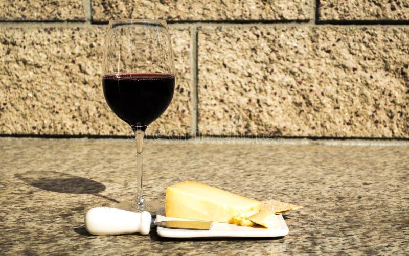 Glas wijn met cheddarkaas, klein mes, en crackers op een openluchtlijst stock foto's