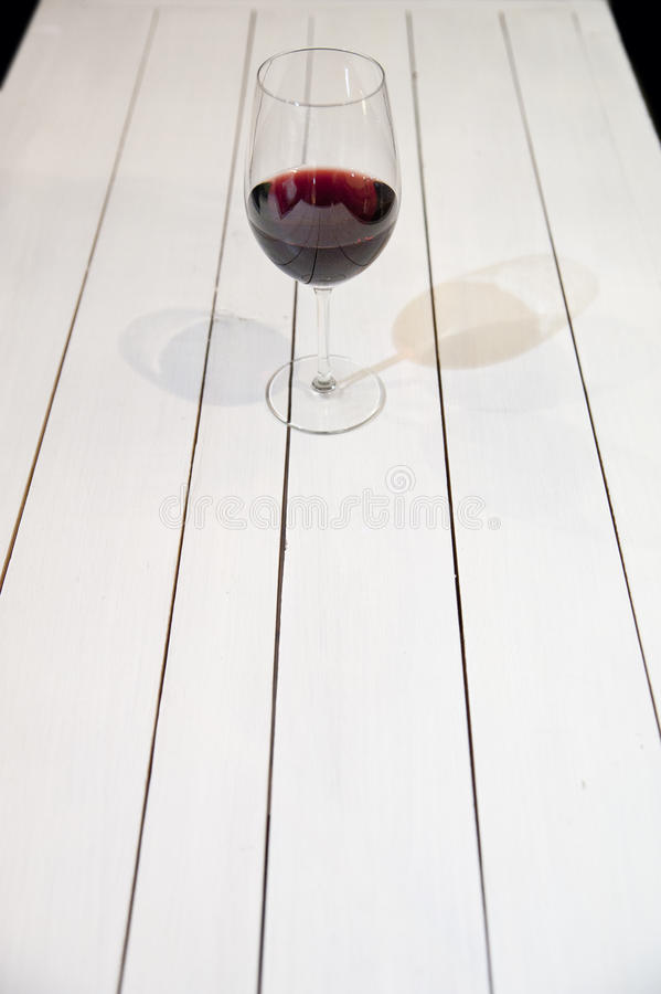 GLAS OF WINE ON WHITE WOODEN TABLE. Glass of red wine on white wooden table royalty free stock photo