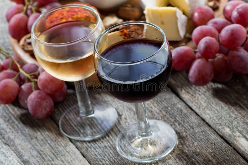 Glas witte en rode wijnen, voorgerechten op een houten lijst royalty-vrije stock foto's