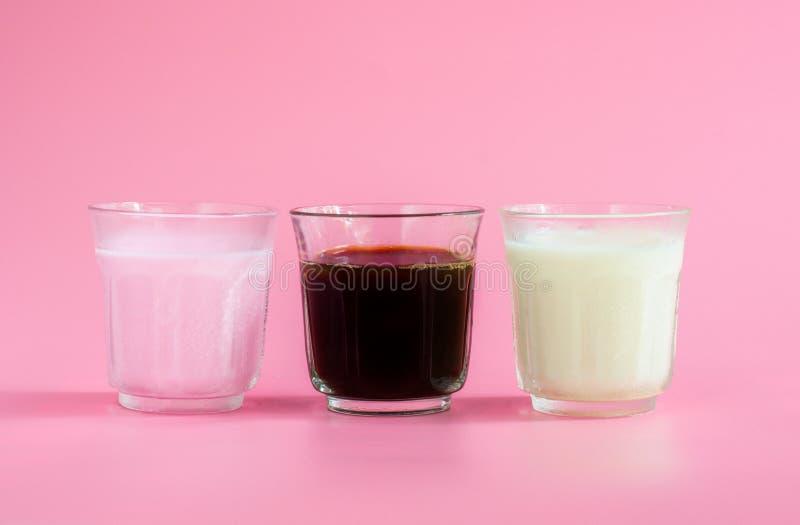 Glas witte en roze melk, zwarte koffie op roze achtergrond Drank in ochtendconcept royalty-vrije stock fotografie