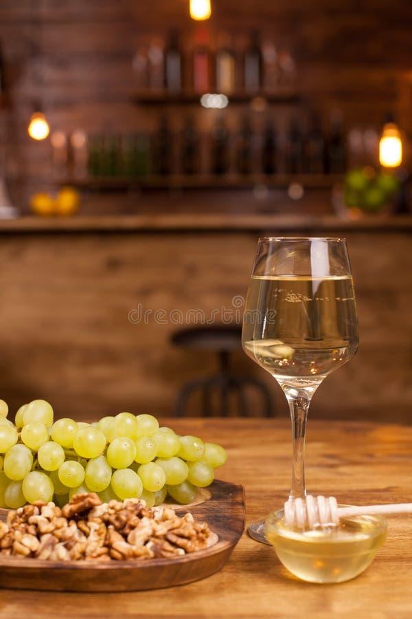 Glas witte wijn met verse druiven en wolnuts op een houten plaat in een uitstekend restaurant stock foto