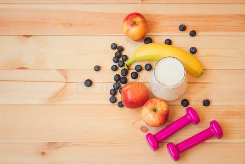 Glas yoghurt, domoren, appelen, banaan en bosbessen op houten achtergrond Gezond levensstijlconcept Selectieve nadruk royalty-vrije stock fotografie