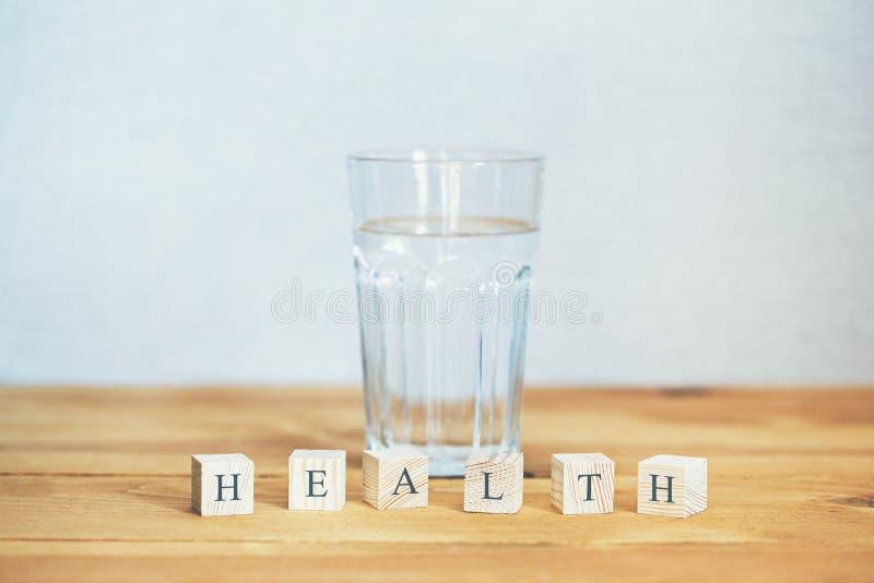 Glas zuiver die water met gezondheidswoord in blokken wordt geschreven stock foto
