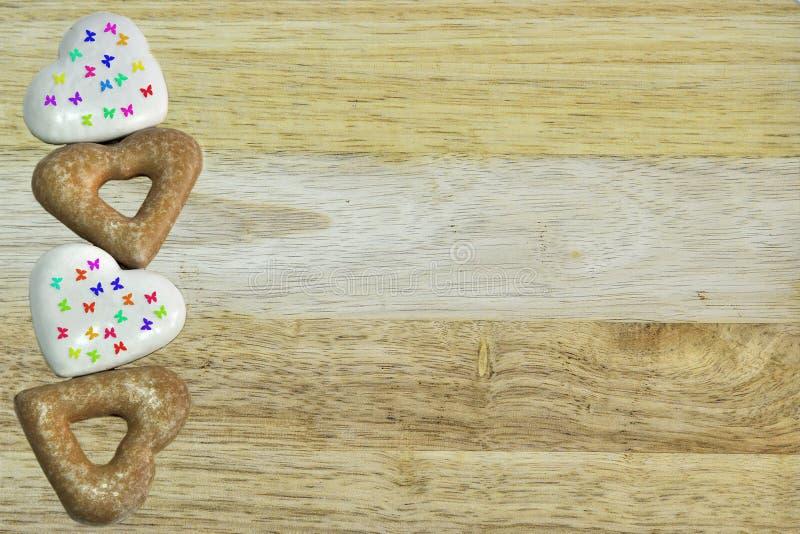 Glasad hjärta formade vita och bruna kakor på en träbakgrund arkivfoto