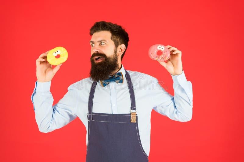 glasad munk Sk?ggig v?l ansad man i f?rkl?det som s?ljer donuts Munkmat bakade godor bakar ihop s?tsaker Skr?pmat fotografering för bildbyråer