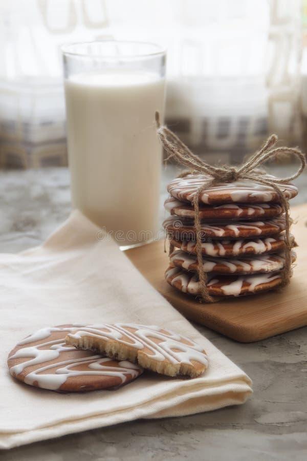 Glasade kakor och ett exponeringsglas av mjölkar arkivfoto