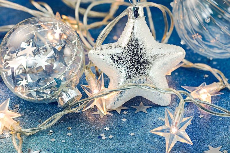 Glasballen met zilveren ster en Kerstmislichten op blauwe backgr stock foto's