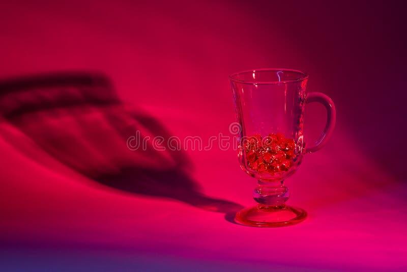 Glasbecher in der roten Beleuchtung stockbilder
