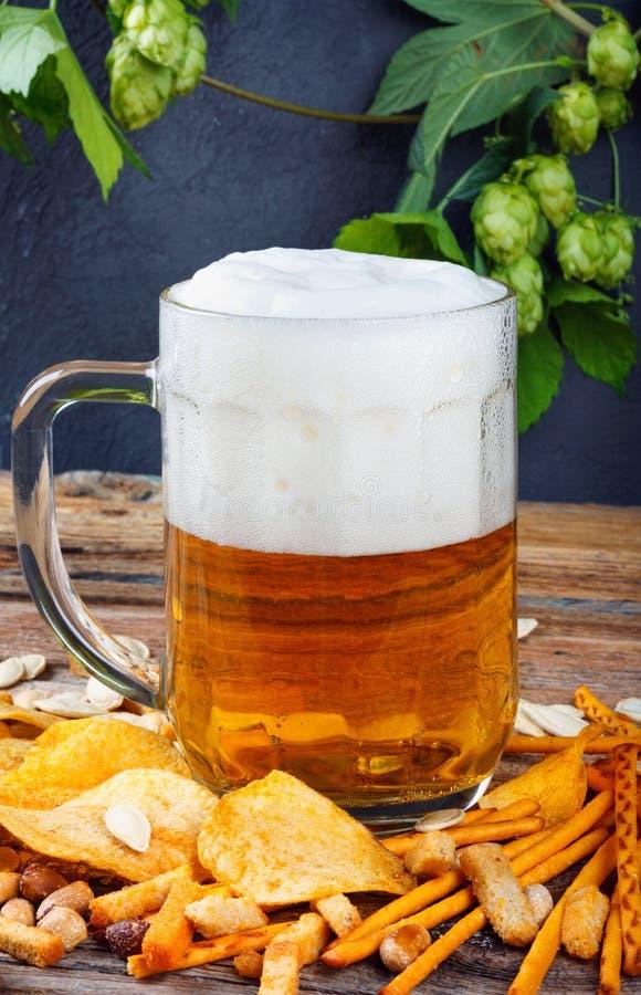 Glasbecher kaltes frisches goldenes Bier mit Crackern und Chips auf Holztisch und Niederlassungen von reifen Hopfen stockfotos