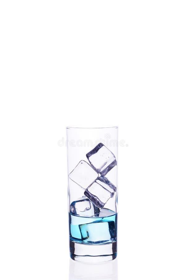 Glasbecher wird mit Würfeln eines blauen Cocktaileises auf einem weißen Hintergrund gefüllt lizenzfreie stockfotos
