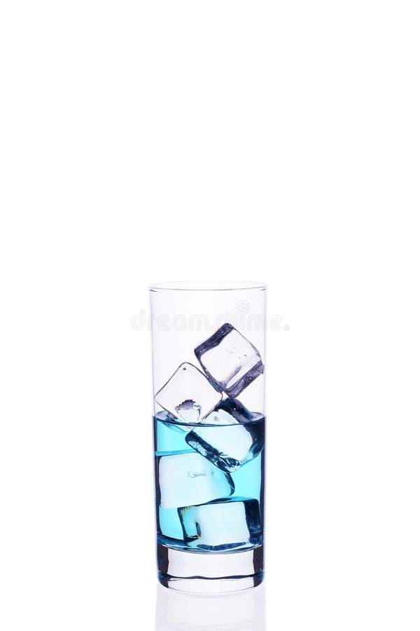 Glasbecher wird mit Würfeln eines blauen Cocktaileises auf einem weißen Hintergrund gefüllt stockfotos