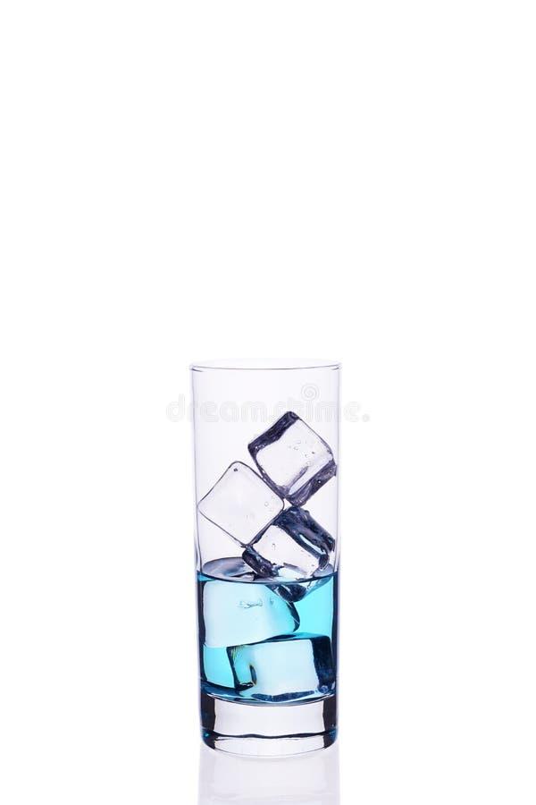 Glasbecher wird mit Würfeln eines blauen Cocktaileises auf einem weißen Hintergrund gefüllt lizenzfreie stockfotografie