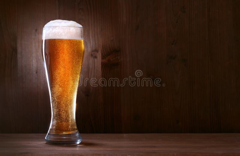 Glasbier auf hölzernem Hintergrund stockfoto