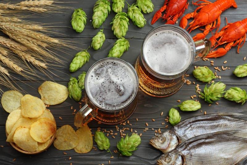 Glasbier met rivierkreeften, droge vissen en hopkegels op donkere houten achtergrond Het concept van de bierbrouwerij De achtergr royalty-vrije stock fotografie