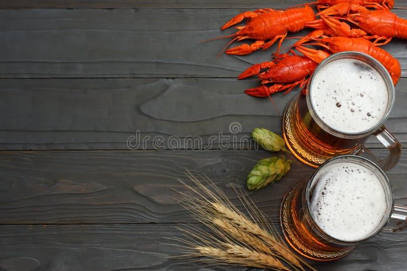 Glasbier met rivierkreeften, hopkegels en tarweoren op donkere houten achtergrond Het concept van de bierbrouwerij De achtergrond stock foto's