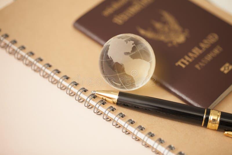 Glasbol en een paspoort met pen op het boek stock foto's