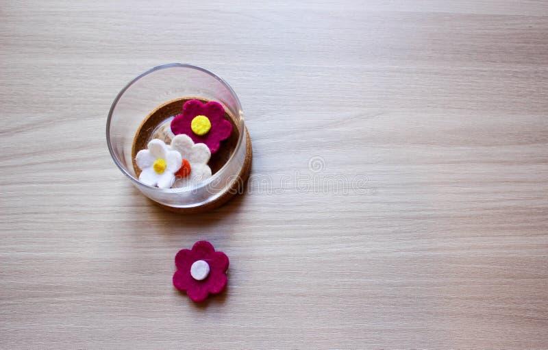 Glascontainers met Tuin gevoelde bloemen over houten achtergrond royalty-vrije stock fotografie