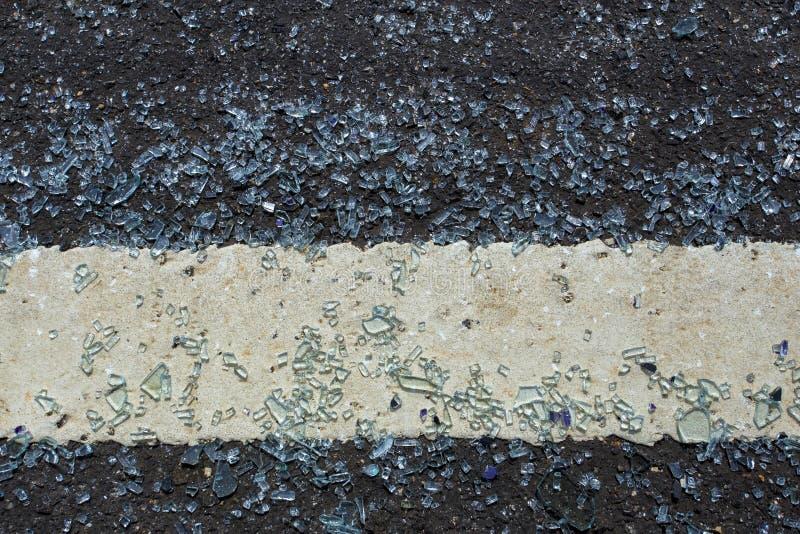 Glasdalingen op de weg en gebroken Het verbrijzelde glas werd uitgespreid uit op de weg Het is gekomen gevaarlijk moet zorgvuldig royalty-vrije stock fotografie