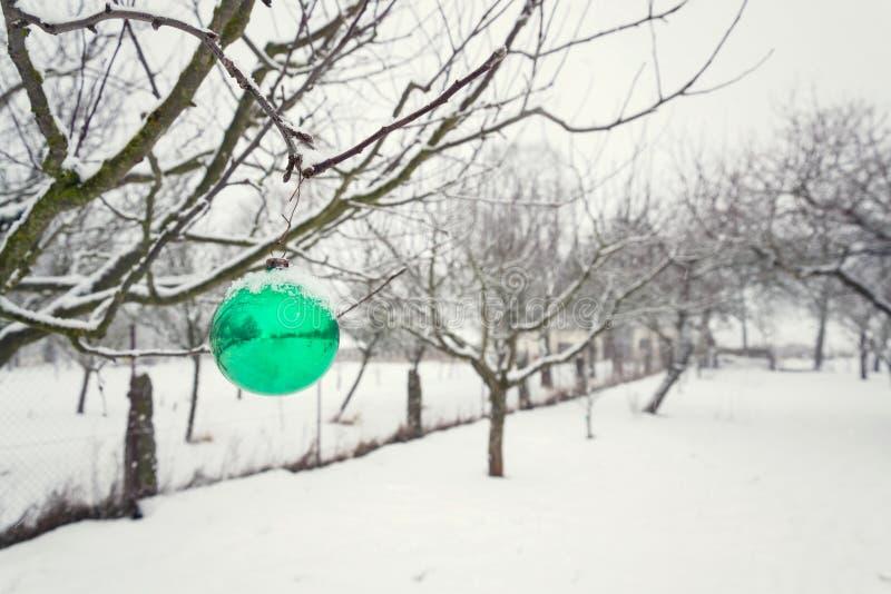 Glasdekoration der grünen Weihnachtsball-Weinlese, die draußen am Baum, fallende Schneewinterlandschaft hängt stockfoto