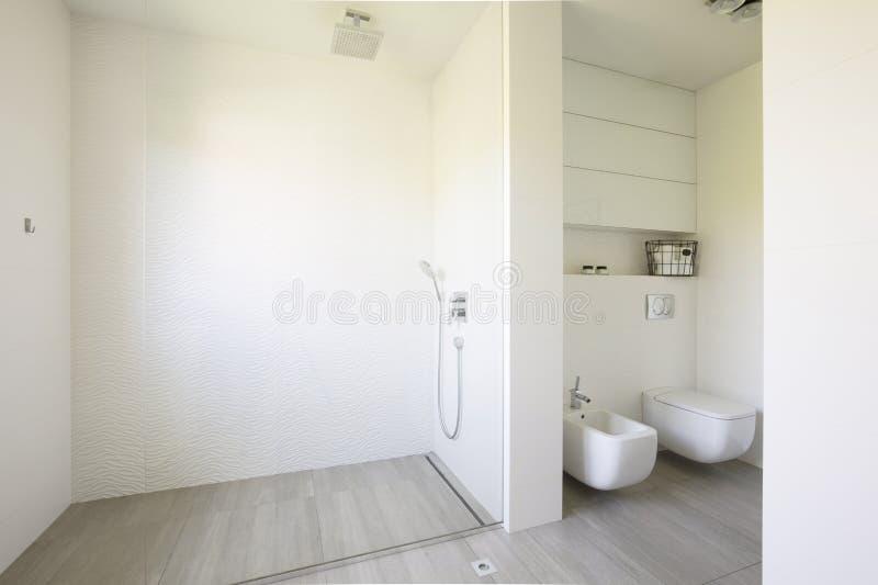 Glasdusche und Toilette im weißen geräumigen Badezimmerinnenraum rea stockfoto