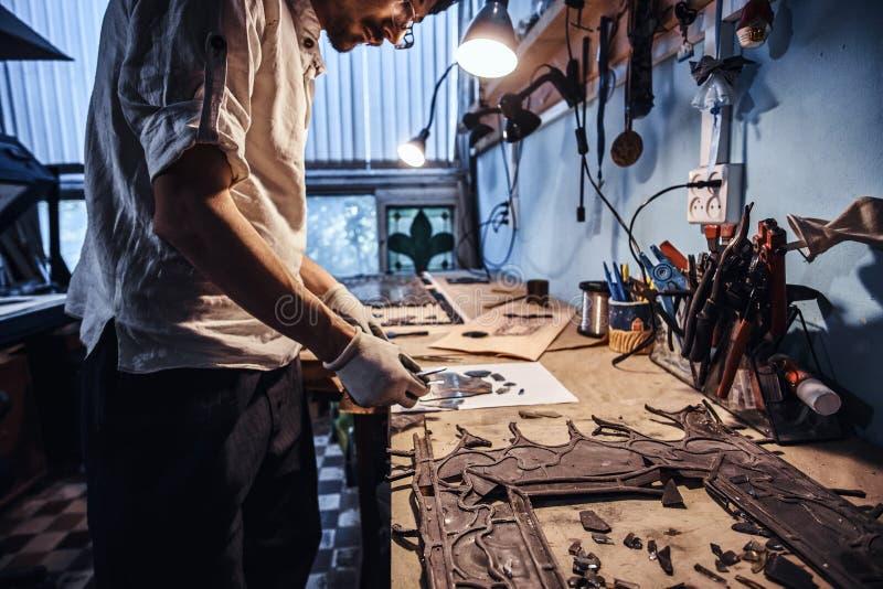 Glaser arbeitet an alter defekter Buntglaswiederherstellung stockfotografie