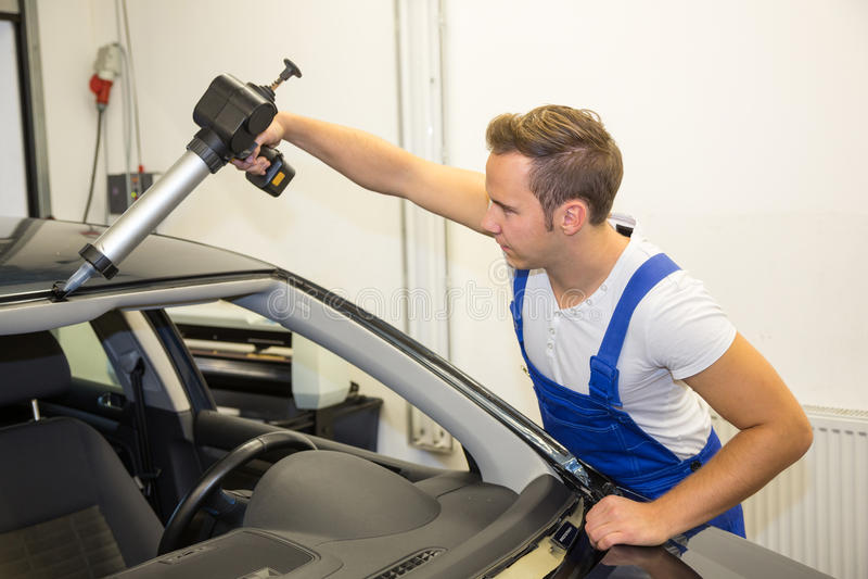 Glaser mit Anwendungsgewehr in der Garage, die Windschutzscheibe oder Windfang ersetzt lizenzfreie stockfotos