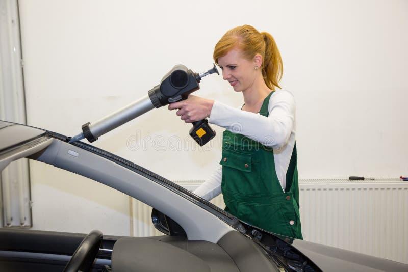 Glaser mit Anwendungsgewehr in der Garage, die Windschutzscheibe oder Windfang ersetzt lizenzfreies stockbild