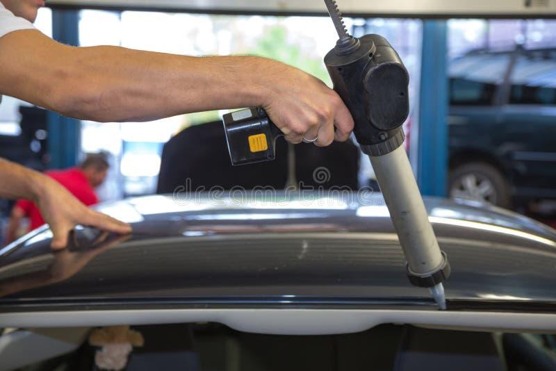 Glaser mit Anwendungsgewehr in der Garage, die Windschutzscheibe oder Windfang ersetzt lizenzfreies stockfoto