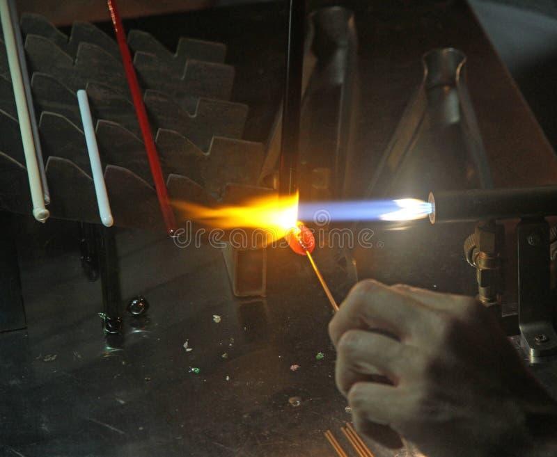 Glaser mit der Gasfackel bei der Mischung einer Glasplatte 2 beleuchtet stockfoto