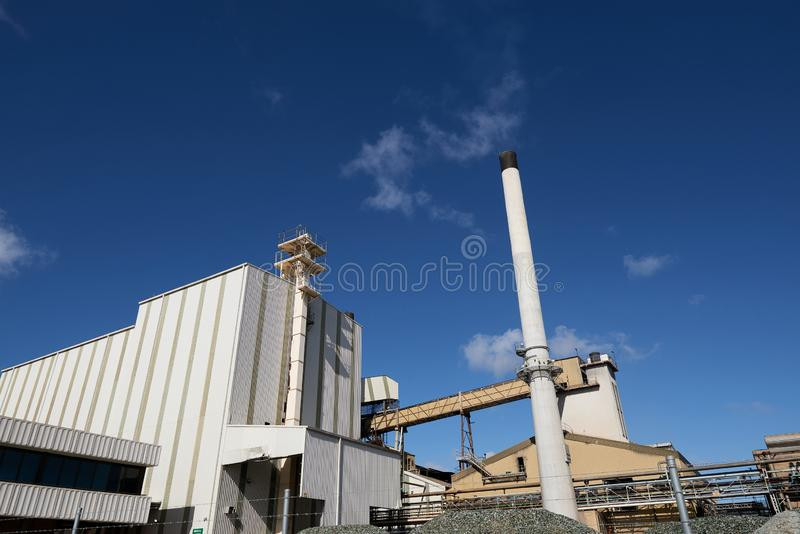 Glasfabriekgebouwen met een schoorsteen op een zonnige blauwe hemeldag stock afbeeldingen
