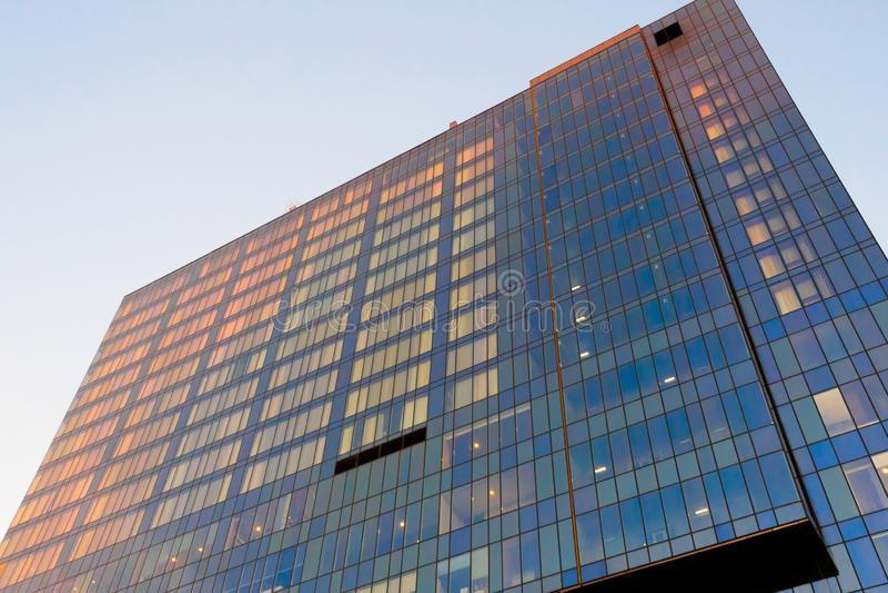 Glasfasaden i en flervåningsbyggnad vid solnedgången, fönstren återspeglar solens orange ljus För design på temat för royaltyfri bild