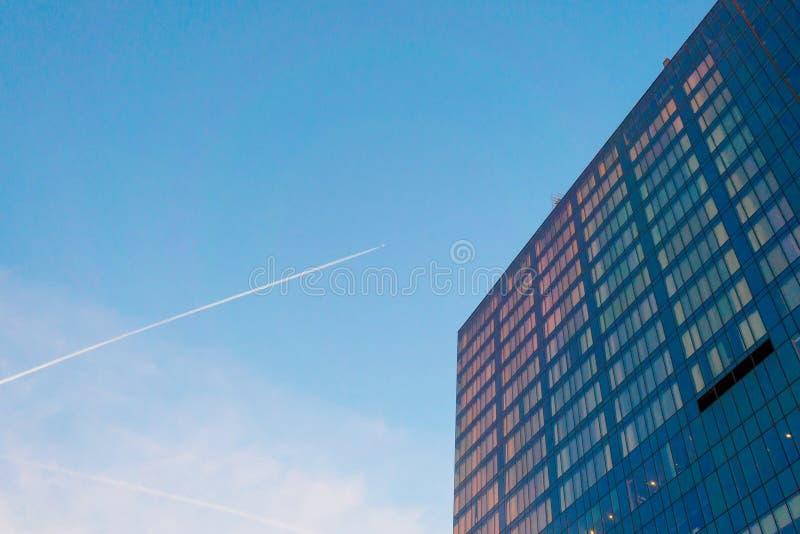 Glasfasaden i en flervåningsbyggnad vid solnedgången, fönstren återspeglar solens orange ljus För design på temat för royaltyfria foton