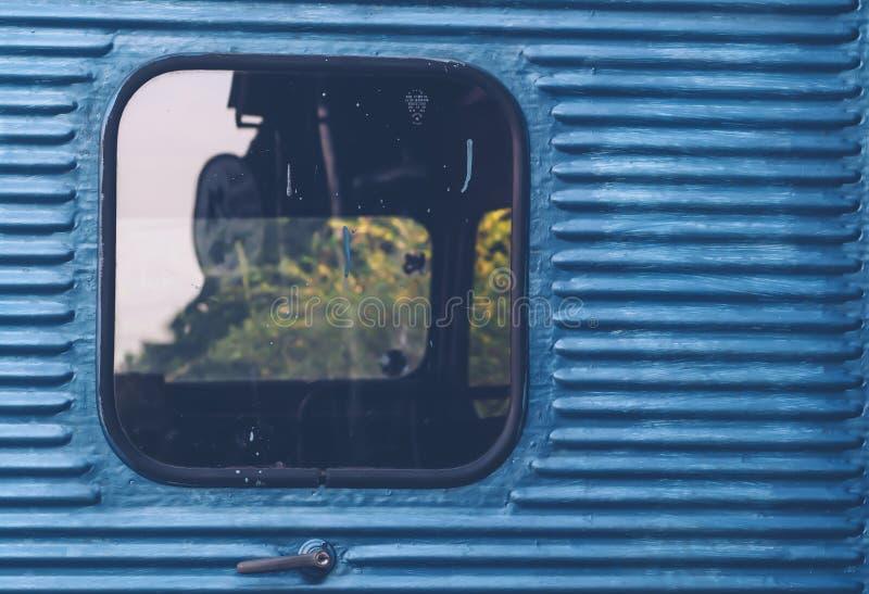 Glasfenster des alten Weinlesezugs mit blauem Behälterzusammenfassungs-Reisehintergrund stockfotos