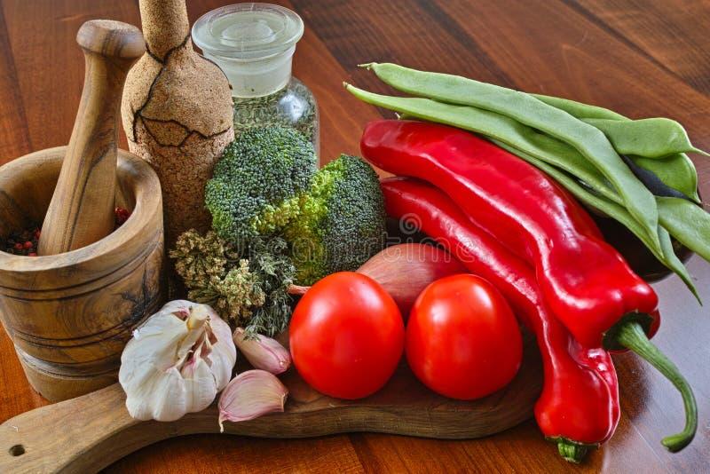 Glasflasche mit Gewürzen, Korkenflasche, olivgrünes hölzernes Mörser-, Rotes und Grünesgemüse, Brokkoli, Tomaten, Knoblauch, Zwie stockfoto