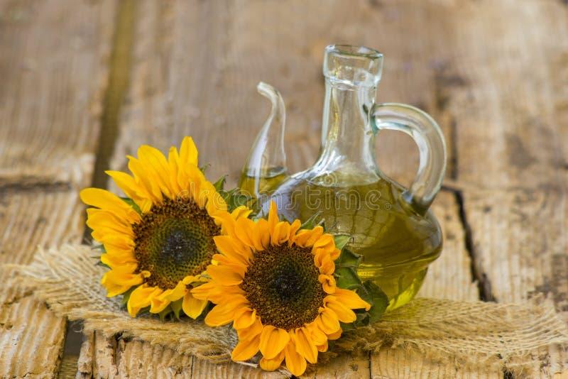 Glasflasche mit Sonnenblumen?l und Sonnenblumen stockfoto