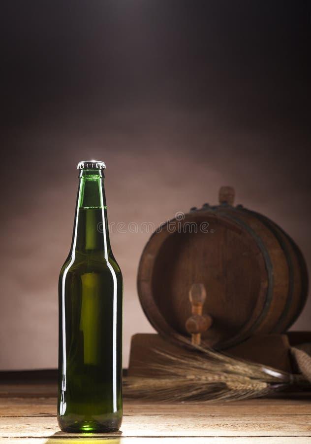 Glasflaska av öl och trätrumman på brun bakgrund royaltyfri foto