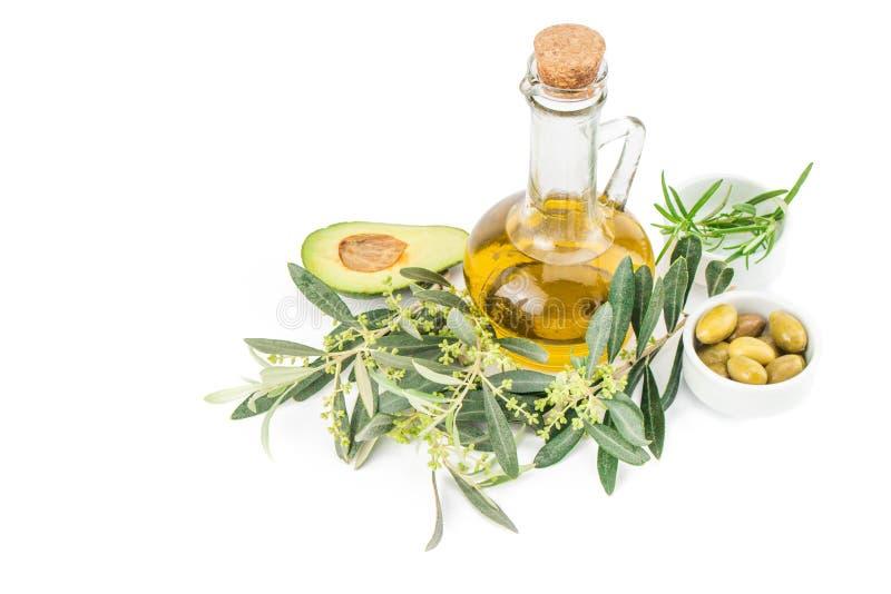 Glasflaska av högvärdig jungfrulig olivolja, avokado, rosmarin och några oliv med den olivgröna filialen royaltyfri fotografi