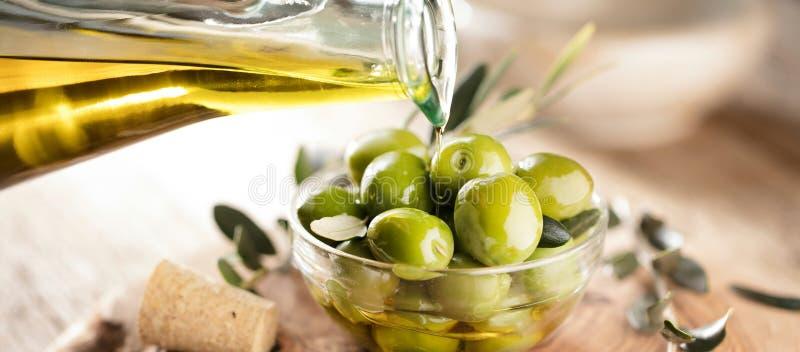 Glasflaska av högvärdig jungfrulig olivolja och några oliv med le royaltyfria bilder