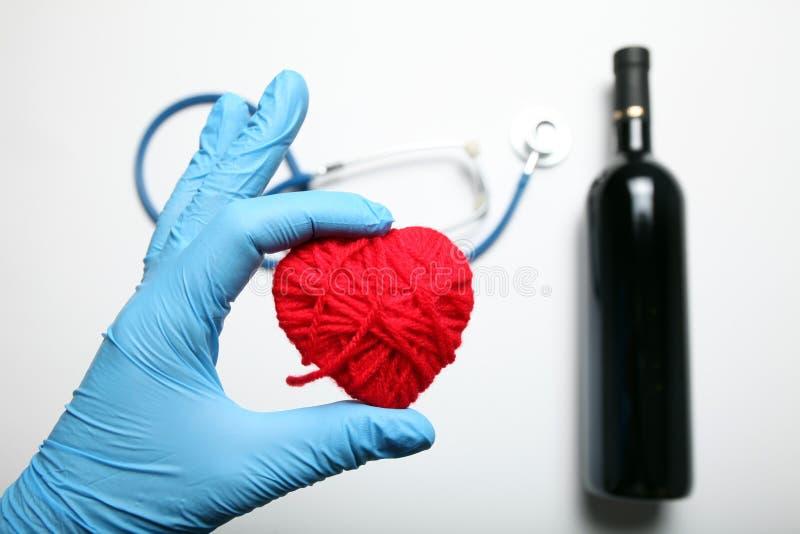 Glasflaska av r?tt vin och stetoskopet F?rhindrande av hj?rtsjukdomen arkivfoton
