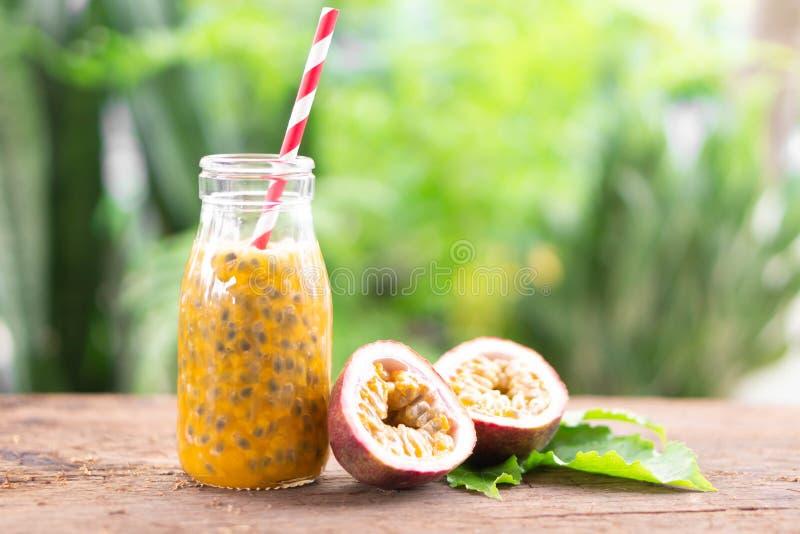 Glasflaska av tabellen för trä för passionfruktfruktsaft med grön naturbakgrund, sunt begrepp för mat arkivbild