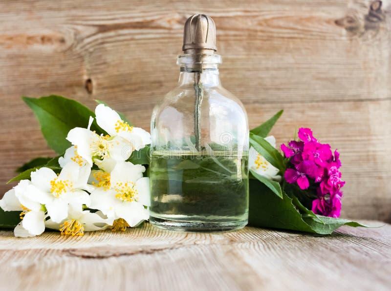 Glasflaska för olja för arom för Spa doft nödvändig med blommablomningar på gammal träbakgrund royaltyfri bild
