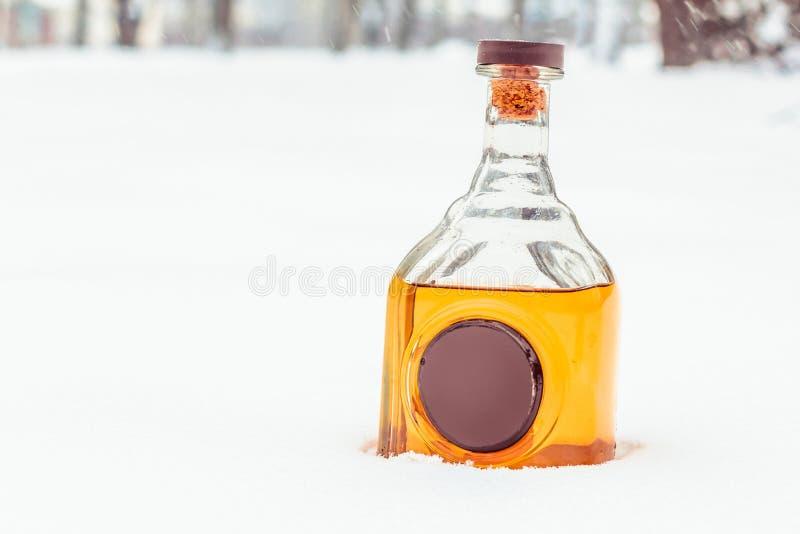 Glasflaska med elitalkohol och vaxskyddsremsan i snön royaltyfria foton